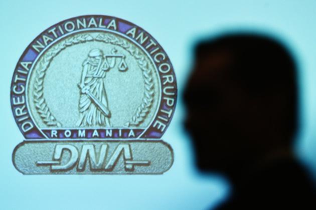 Umbra unei persoane este proiectata pe un panou cu sigla Directiei Nationale Anticoruptie (DNA), in timpul evenimentului de prezentare a Raportului anual de activitate al institutiei pe anul 2014, in Bucuresti, marti, 24 februarie 2015. CODRIN PRISECARU / MEDIAFAX FOTO